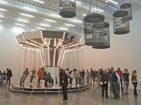 The Carsten Holler carousel with public riders and a canary mobile in New York's New Museum