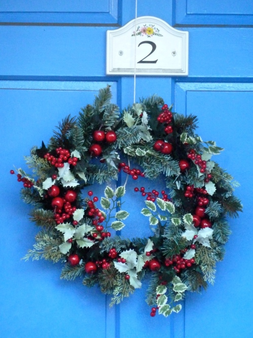 Another classic wreath looking strong against a bright blue door for Christmas 2011