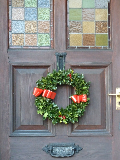 A simple Holly wreath, holly bushes are common in this area and I wonder if they made it themselves, for Xmas 2011